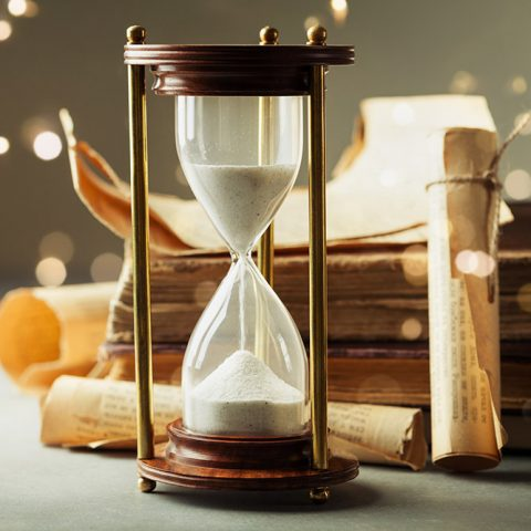 Sand running through the hourglass and old vintage books. Time k