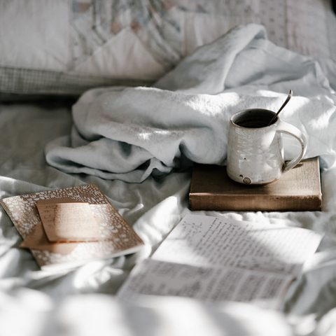 A close-up photo of the corner of a messy bed, with a coffee mug sitting atop a brown book next to an open journal