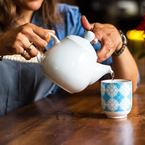 A person pouring hot water into a tea mug