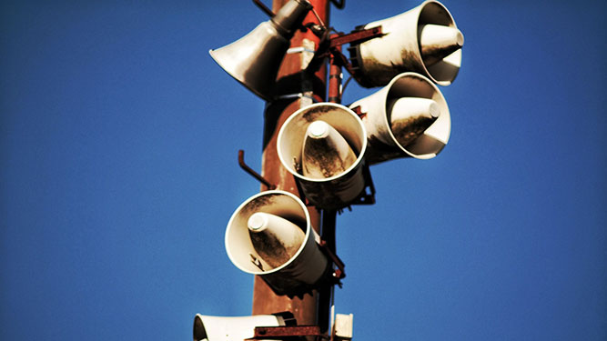 A wooden pole adorned with several white loudspeakers pointing in every direction, in front of a blue sky.
