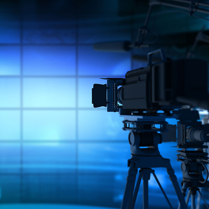 News Camera with blue background pointing at a live set