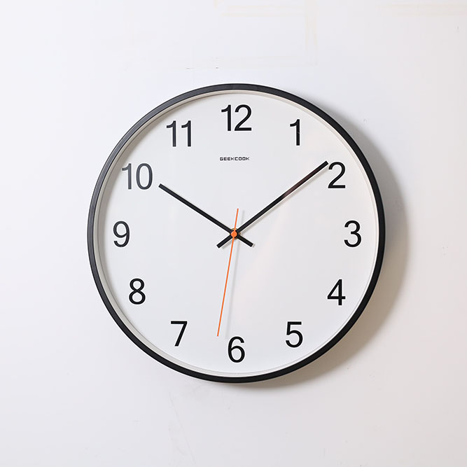 A round analog wall clock with a white face and black hands points to 10:09