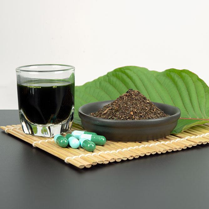 Fresh Kratom Leaf, Kratom Powder, Kratom Capsules, and Kratom Extract on nice bamboo plate