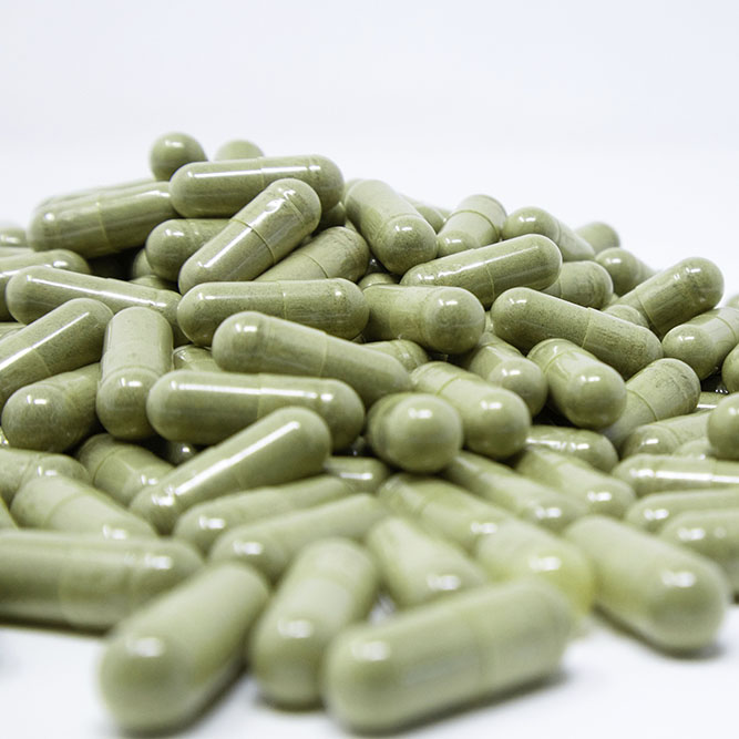 A pile of capsules filled with green Malay kratom powder.