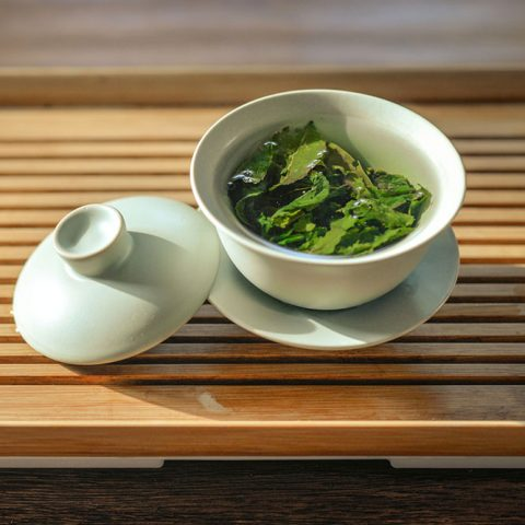 A white teacup, with its top resting on its side, is full of green tea and sits atop a wooden serving tray on a table