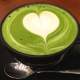 A photo of a teacup filled with a green liquid, with the shape of a white heart visible in the foam.