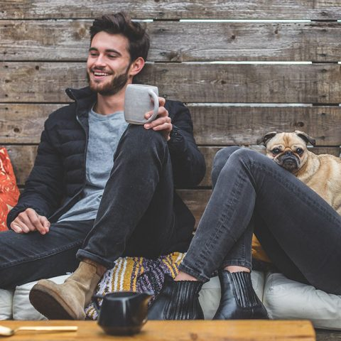 A photo of two people reclining on a bench and smiling while holding coffee cups.