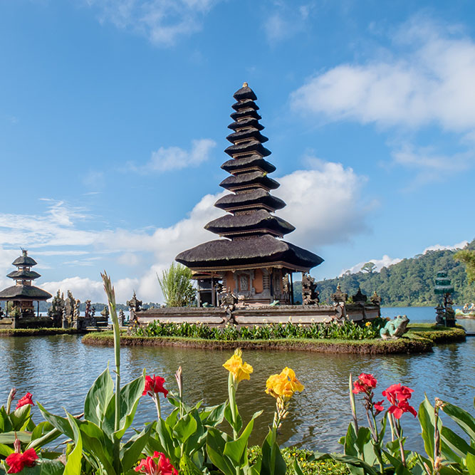 A Balinese temple on the water, with yellow and red flowers in the foreground.
