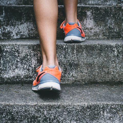 A person wearing grey and orange sneakers runs up a set of concrete stairs