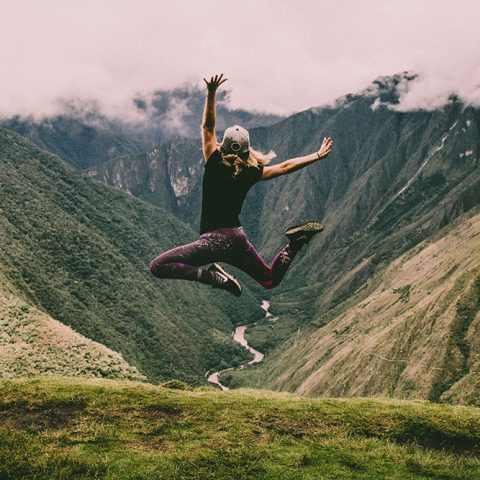 A person jumping on top of a mountain.