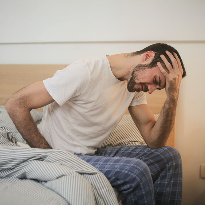 A person holds their head in pain while sitting on the side of their bed.