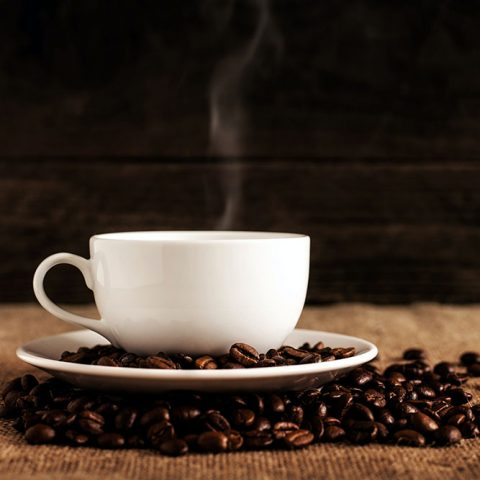 A white mug of steaming coffee on a white saucer covered in coffee beans.