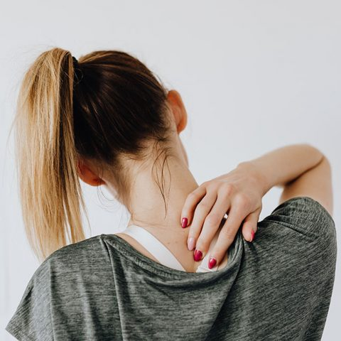 A person with a long blond ponytail faces away from the camera and brings their hand up to their neck to signal physical pain