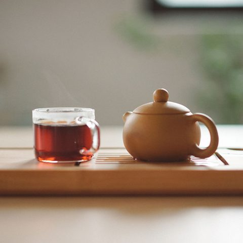 A wooden teapot and a glass mug of tea sitting on a wooden serving tray.