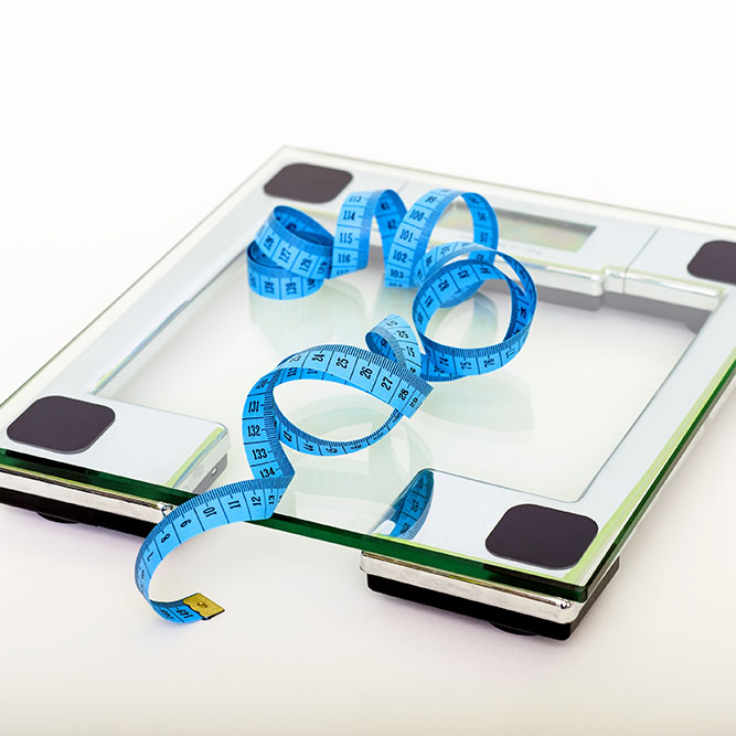 A blue measuring tape unravels on top of a scale.