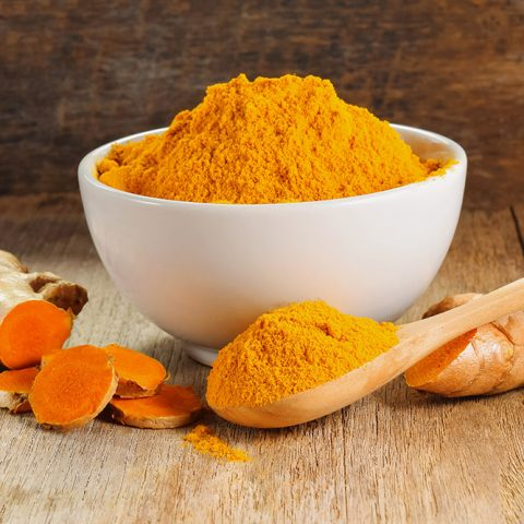 Orange Turmeric Powder in a white bowl with a wooden spoon and tumeric roots